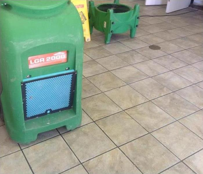 Equipment drying out water damage to tile in commercial building